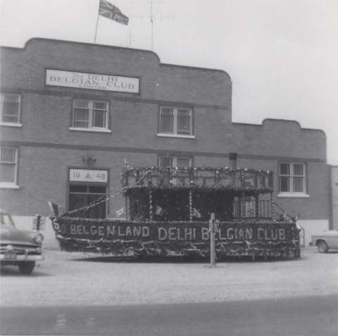 """B/W photo of a parade float in front of the Delhi Belgian Club decorated with """"S.S. BELGENLAND DELHI BELGIAN CLUB"""" along with Belgian and union jack flags"""